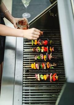 Femme cuisine barbecue végétalien sur un gril à charbon