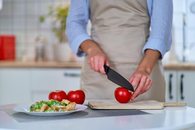 Femme De Cuisine Coupant Des Tomates Juteuses écologiques Fraîches Mûres Sur Une Planche De Bois à L'aide D'un Couteau Photo Premium