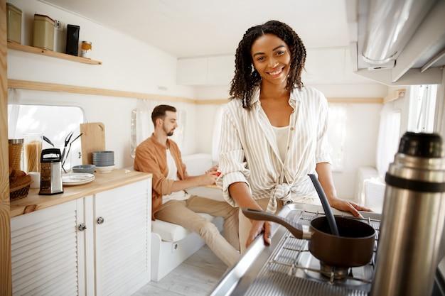 Femme cuisine dans la cuisine rv, camping dans une remorque. homme et femme voyagent en van, vacances romantiques en camping-car, loisirs campeurs en camping-car