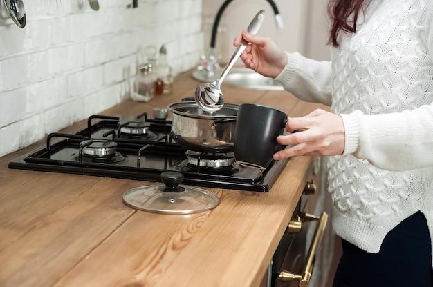 Femme cuisine délicieux vin chaud au poêle gros plan.