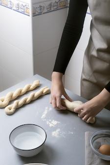 Femme sur la cuisine à domicile prépare la pâte avec de la farine pour faire de la poêle, du pain ou des pâtes bio
