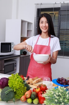 Femme, cuisine, fouetter, oeufs, bol, cuisine, salle