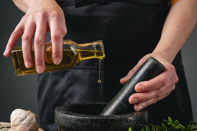 Femme cuisine avec de l'huile d'olive et du mortier dans la cuisine