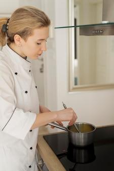 Femme cuisine en pot moyen shot