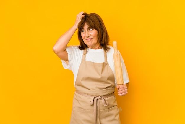 Femme de cuisinier caucasien d'âge moyen tenant un rouleau choqué, elle s'est souvenue d'une réunion importante.