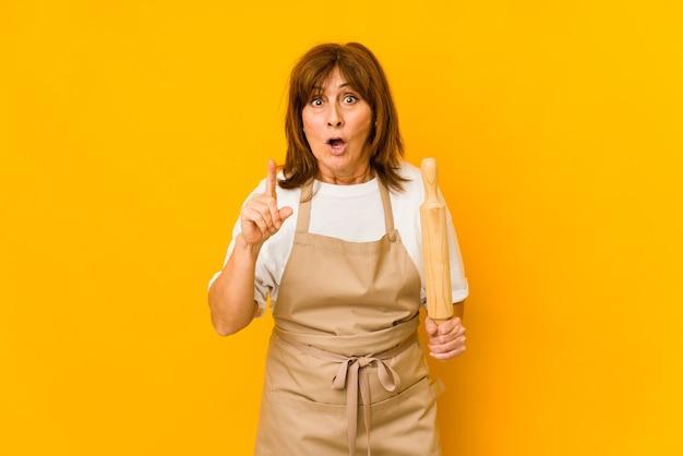 Femme de cuisinier caucasien d'âge moyen tenant un rouleau isolé ayant une idée, un concept d'inspiration.