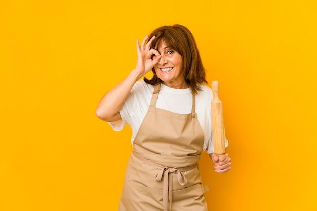 Femme de cuisinier caucasien d'âge moyen tenant un rouleau isolé excité gardant le geste ok sur les yeux.