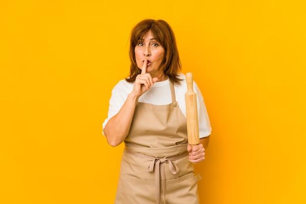 Femme de cuisinier caucasien d'âge moyen tenant un rouleau isolé en gardant un secret ou en demandant le silence.