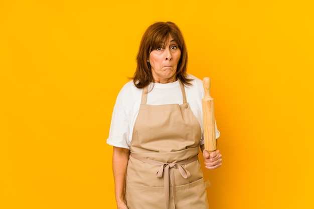 Femme de cuisinier caucasien d'âge moyen tenant un rouleau isolé hausse les épaules et les yeux ouverts confus.