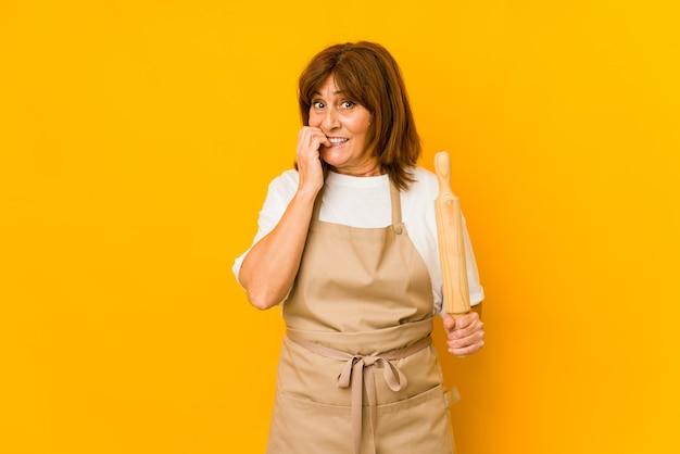 Femme de cuisinier caucasien d'âge moyen tenant un rouleau isolé des ongles mordants, nerveux et très anxieux.