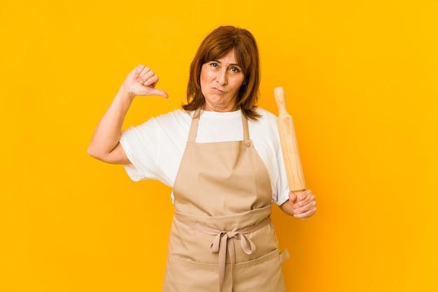 Femme de cuisinier caucasien d'âge moyen tenant un rouleau isolé se sent fier et confiant, exemple à suivre.