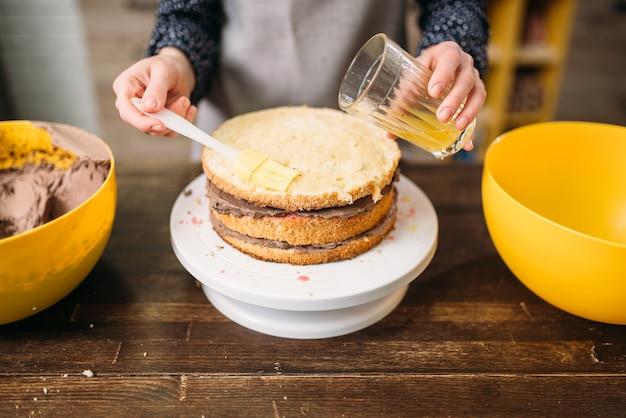 Femme cuisinier mains verse le gâteau avec du sirop de sucre. délicieux dessert cuisine maison