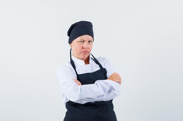 Femme cuisinier en uniforme, tablier debout avec les bras croisés et à l'offensé, vue de face.