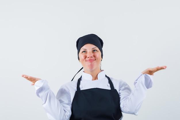 Femme cuisinière faisant le geste des échelles en uniforme, tablier et à la gaieté. vue de face.