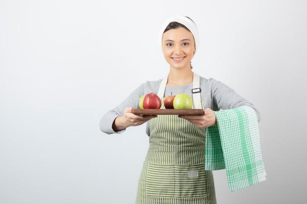 Femme cuisinière souriante en tablier tenant une assiette de pommes sur blanc.