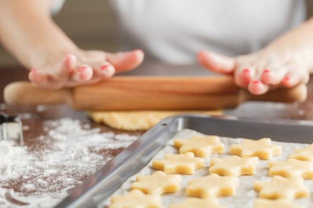 Femme, cuisson des étoiles de pain au gingembre pour noël. couleurs naturelles. vrai vie
