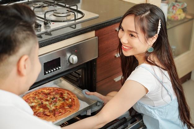 Femme cuit une pizza pour le dîner