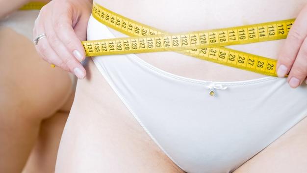 Femme en culotte mesurant sa taille avec un ruban à mesurer jaune