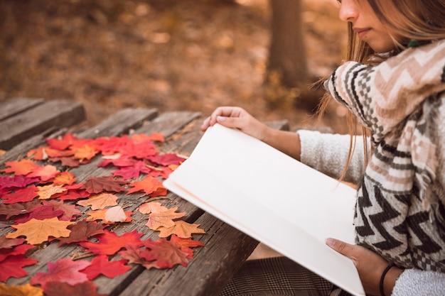 Femme de culture lecture à table dans le parc