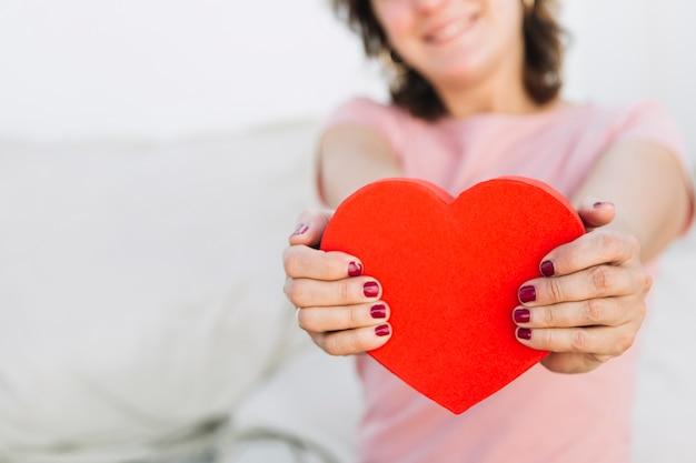 Femme de culture montrant une boîte en forme de coeur