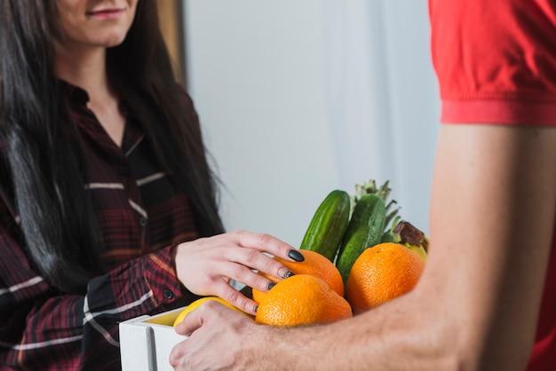 Femme de culture vérifiant les fruits livrés par courrier