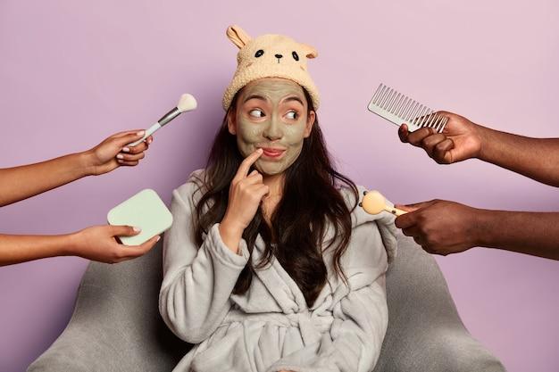 Une femme curieuse et joyeuse se réjouit du nouveau masque anti-rides, prévient les signes du vieillissement cutané