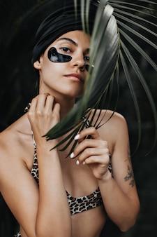 Femme curieuse avec des patchs oculaires regardant la caméra. tir extérieur d'une femme élégante en turban posant sur fond exotique.