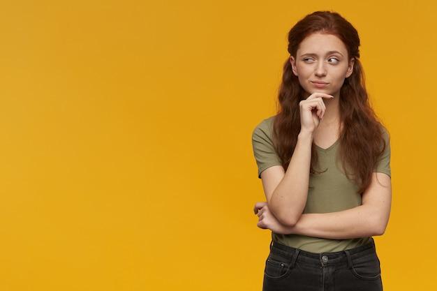 Femme curieuse et pensante aux longs cheveux roux. porter un t-shirt vert. concept d'émotion. touchant son menton et lève les sourcils. regarder vers la gauche à l'espace de copie, isolé sur un mur orange