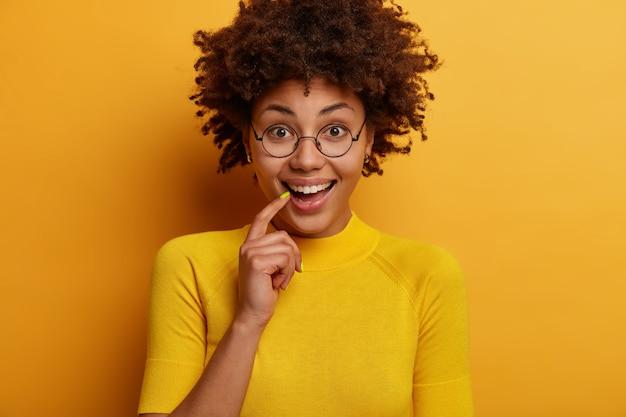 Une femme curieuse positive écoute quelque chose de très intéressant, garde le doigt sur les lèvres, a un regard direct, aime discuter de nouvelles agréables, porte des lunettes, a les yeux pleins d'intérêt et de bonheur
