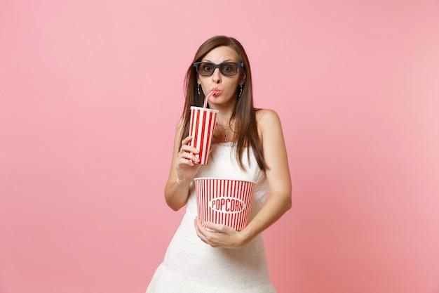 Femme curieuse en robe blanche, lunettes 3d regardant un film tenant un seau de pop-corn, une tasse en plastique de soda ou de cola