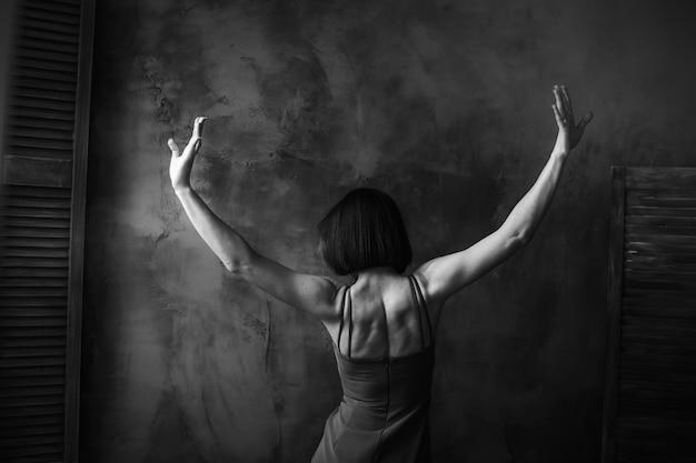Femme curvy écarte ses mains comme un oiseau posant dans une pièce sombre