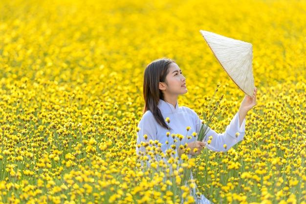 Une femme dans un ancien costume national vietnamien était debout tenant un chapeau en osier parmi les fleurs jaunes