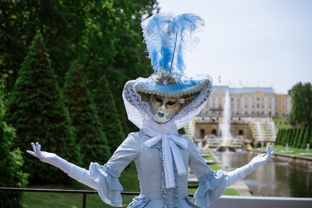 Femme dans une belle robe de carnaval bleu et dans un masque vénitien dans le parc par une journée ensoleillée
