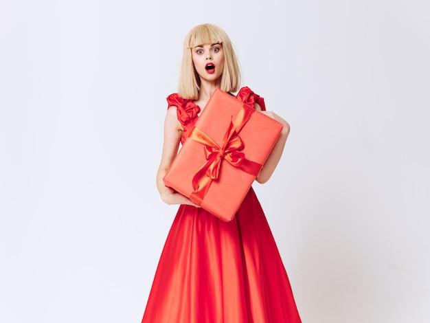 Femme dans une belle robe avec des coffrets cadeaux en studio, vente et célébration