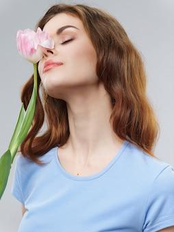 Femme dans une belle robe à fleurs le 8 mars, fleurs cadeaux fond clair saint valentin
