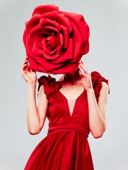 Femme dans une belle robe rouge avec une rose et des pétales de rose sur un espace rouge