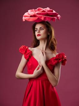Femme dans une belle robe rouge avec une rose et des pétales de rose sur un mur rouge
