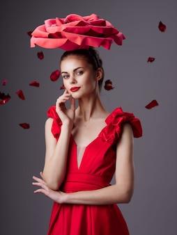 Femme dans une belle robe rouge avec une rose et des pétales de rose sur une surface rouge