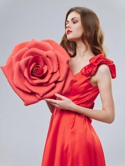 Femme dans une belle robe rouge avec une rose et des pétales de rose