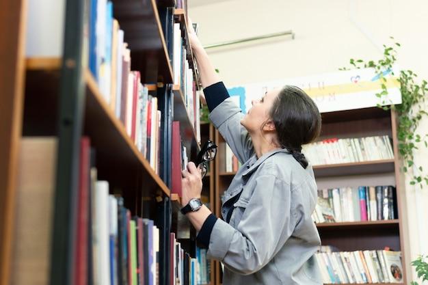 Femme dans la bibliothèque devant les étagères. concept d'éducation