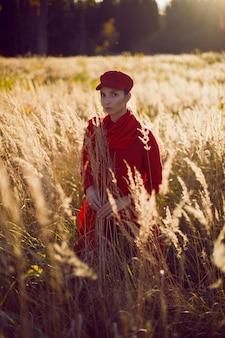 Femme dans un bonnet rouge et une écharpe se dresse dans un champ à l'automne dans les hautes herbes sèches