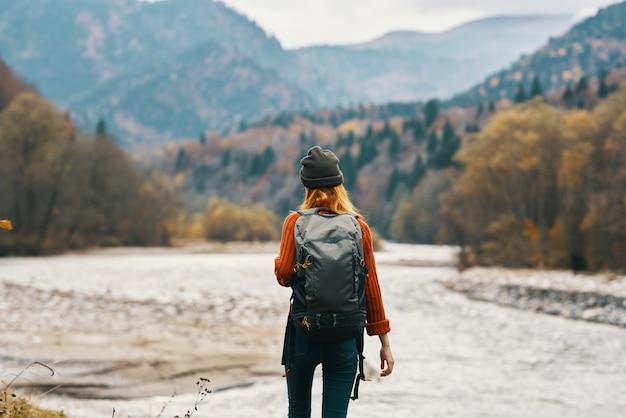 Femme dans un bonnet rouge avec un sac à dos sur la rive du fleuve et les montagnes au loin
