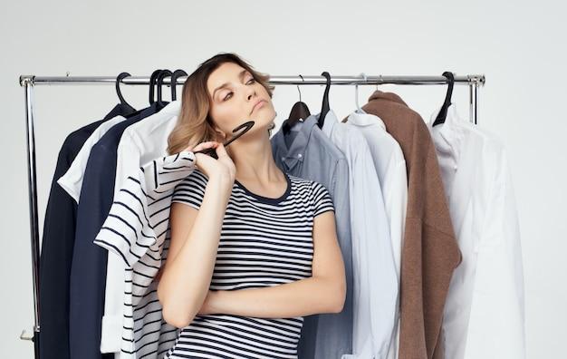 Femme dans la cabine d'essayage avec des vêtements en chemise à la main. photo de haute qualité