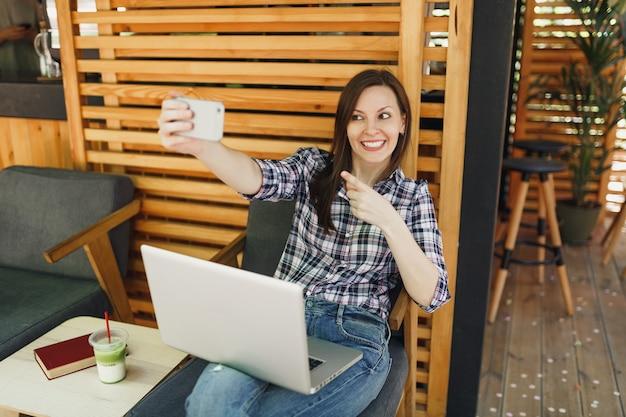Femme dans un café d'été en bois à l'extérieur de la rue assise avec un ordinateur portable, faisant une photo de selfie sur un téléphone portable, se relaxant pendant le temps libre. bureau mobile