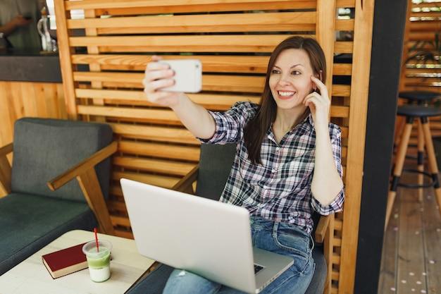 Femme dans un café d'été de rue en bois à l'extérieur assis avec un ordinateur portable, faisant un selfie sur un téléphone portable