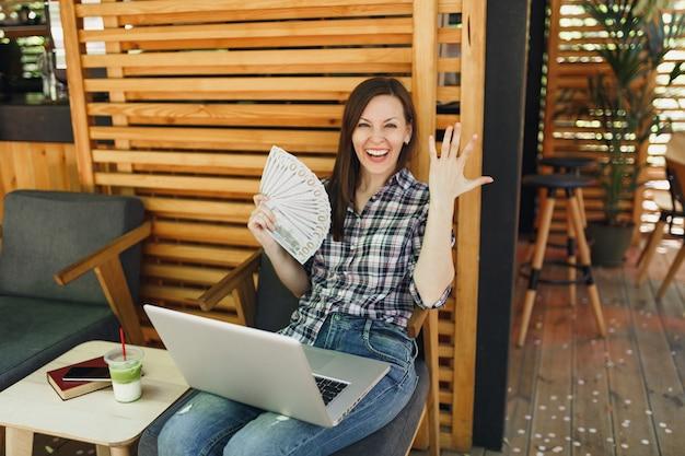 Femme dans un café de la rue en plein air assis avec un ordinateur portable moderne, tenir dans la main un tas de billets de banque en dollars, de l'argent en espèces
