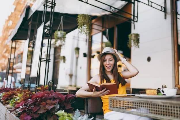 Femme dans un café de rue en plein air assis à table dans un chapeau, lisant un livre avec une tasse de cappuccino, un gâteau, se relaxant au restaurant pendant le temps libre