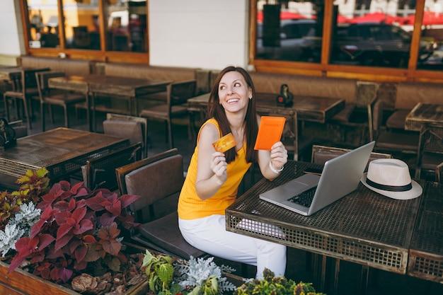 Femme dans un café de rue en plein air assis à table avec un ordinateur portable moderne, tient en main une carte de crédit bancaire et un passeport