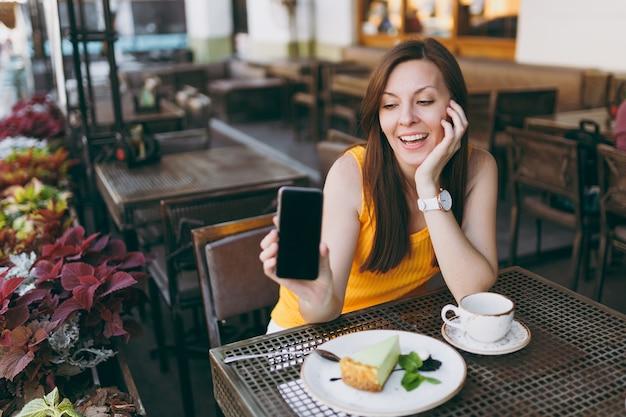 Femme dans un café de rue en plein air assis à table avec une tasse de thé, un gâteau, tenir dans la main un téléphone portable avec un écran vide vierge