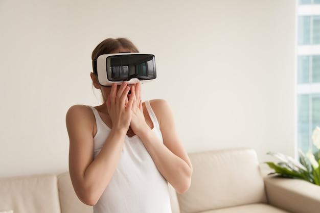 Femme dans le casque de réalité virtuelle effrayée par des effets réalistes